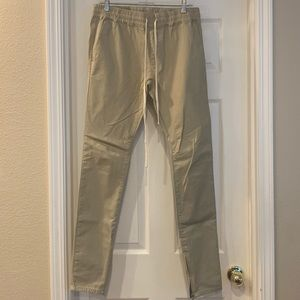Tan cotton joggers with zippers around the ankles